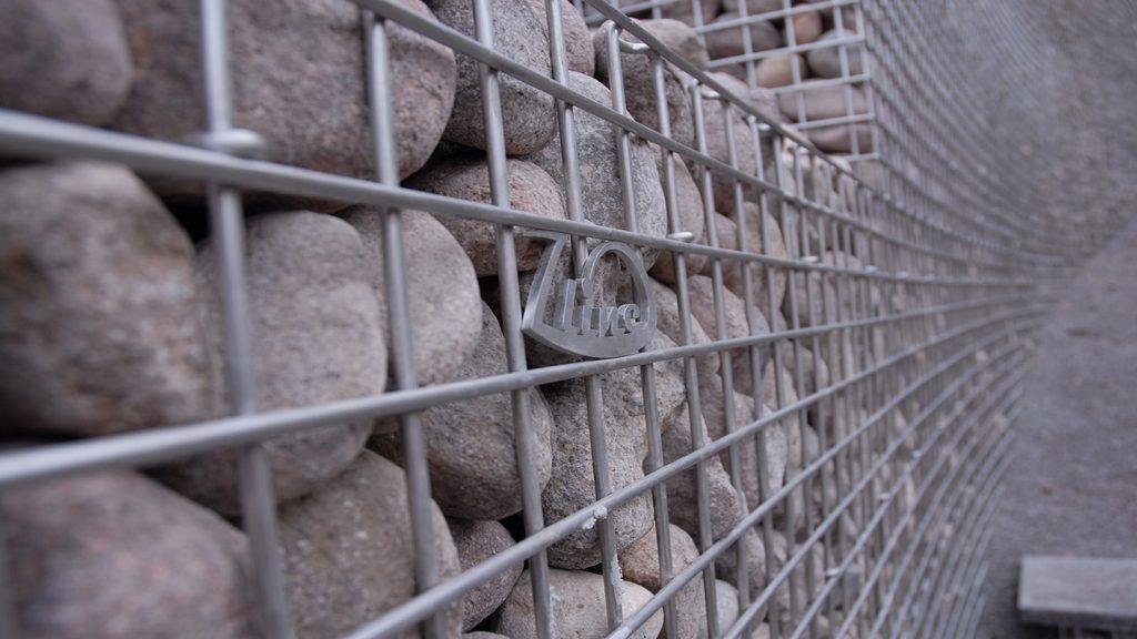 Dettaglio muro in acciaio inox e ciottoli